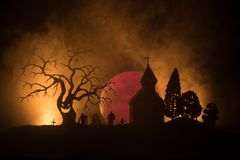 Scary view of zombies at cemetery dead tree, moon, church and spooky cloudy sky with fog, Horror Halloween concept. stock photography