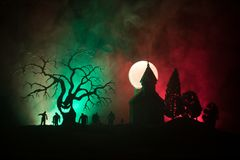 Scary view of zombies at cemetery dead tree, moon, church and spooky cloudy sky with fog, Horror Halloween concept. Toned stock photography