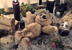 Scary voodoo doll with paper scrolls and black candles Royalty Free Stock Image