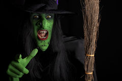 Scary witch. Scary witch pointing at camera with her broomstick. Low key lighting stock photos