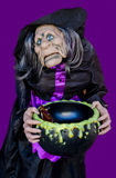 Scary witch with cauldron for candy Stock Images