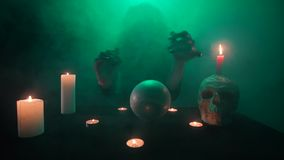 Scary witch in green smoke, conjuring on a crystal ball, occult table with a skull and candles, fast motion