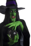 Scary witch with her crystal ball. Scary witch with her crystal ball, isolated on white Royalty Free Stock Images