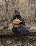 Scary witch on the log with pumpkin. Halloween background with scary witch in black mantle sitting with pumpkin on the old log in the forest Royalty Free Stock Photos