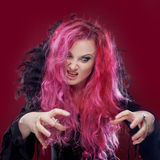 Scary witch with red hair performs magic. Halloween. Stock Images