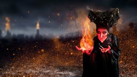 Scary witch summoning a spell. In a dark environment Stock Photography
