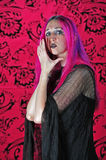 Scary witchy looking woman cups her face. A beautiful young woman in a long black dress and purple hair with a black shawl over her shoulders, holds her hands in Royalty Free Stock Images