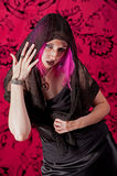 Scary witchy woman. A beautiful young woman in a long black dress and purple hair with a black shawl over her head, moves her hand with a spider ring and Royalty Free Stock Photo