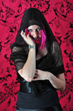 Scary witchy woman smiling. A beautiful young woman in a long black dress and purple hair with a black shawl over her head, moves her hand with a spider ring and Royalty Free Stock Photography