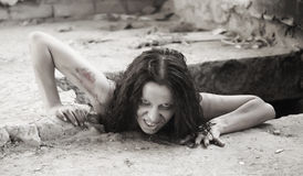 Scary woman. Creeping out of a hole Stock Photos