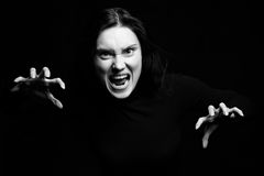 Scary woman in B & W. Scary woman with open mouth and claw like hands coming out of a black background Royalty Free Stock Photo