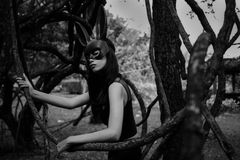 Scary woman with bunny mask in wood. Portrait of beautiful Asian scary woman with fit black dress outfit and rabbit bunny ear mask at old tree in forest with stock photography