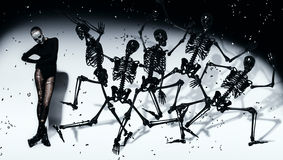 Scary woman with dancing black skeletons. In studio Stock Photo