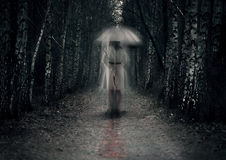 Scary woman ghost with knife. Stays in dark forest path Royalty Free Stock Image