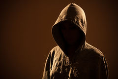 Scary woman with hood in darkness Stock Photo