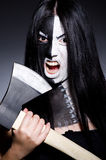 Scary woman with metal axe. In halloween concept Royalty Free Stock Image