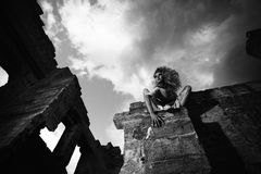 Scary woman in the ruins, view from below. Fantasy style portrait of a scary woman sitting on the ruined wall, view from below, black and white shot Stock Image