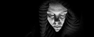 Scary Woman in Shroud, Panorama. An ugly, scary looking woman in a black shroud; her eyes are closed as if in despair; very shadowy harsh image; black and white Royalty Free Stock Photo