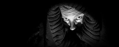Scary Woman in Shroud, Panorama. An ugly, scary looking woman in a black shroud; looks like she is  in despair; very shadowy harsh image; black and white Royalty Free Stock Photos