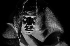 Scary Woman in Shroud, Shadows. An ugly, scary looking woman in a burlap shroud; very shadowy harsh image; black and white horizontal format Royalty Free Stock Photography
