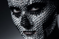 Scary woman with skull face of rhinestones. In studio Royalty Free Stock Images