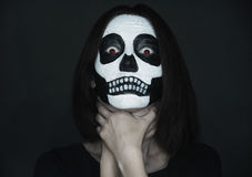 Scary woman with skull make-up. Choking herself on black background. Halloween face art Stock Photography