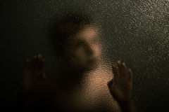 Scary Young Boy Leaning Against a Textured Glass Stock Images
