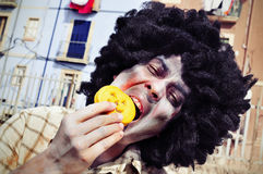 Scary zombie eating a pumpkin-shaped cookie Royalty Free Stock Image