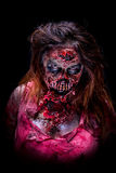 Scary zombie girl. Portrait of a scary zombie girl staring with bloody makeup and latex prosthesis royalty free stock image