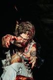 Scary zombie man. With beard creepy vampire or bloody war soldier with wounds and red blood outdoors on dark background Royalty Free Stock Photo