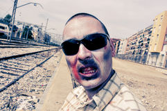 Scary zombie with sunglasses at abandoned railroad tracks, with Royalty Free Stock Photos