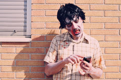Scary zombie using a smartphone Stock Photography