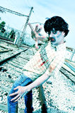 Scary zombie walking by the railroad tracks Stock Photo