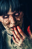 Scary zombie woman. With white eyes and bloody hand royalty free stock photo