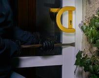Scassinatore che prova ad entrare in una casa facendo uso di un bastone a leva immagini stock