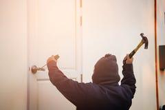 Scassinatore che prova a rompersi in una casa con un martello e immagine stock libera da diritti