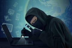 Scassinatore che ruba i dati utenti sul computer portatile Fotografie Stock
