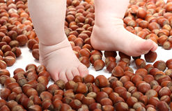 Scaterring nuts and baby's feets Royalty Free Stock Photography