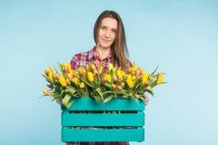 Scatola allegra della tenuta del fiorista della giovane donna dei tulipani immagini stock