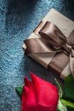 Scatola attuale con la rosa rossa marrone dell'arco sulle feste nere del fondo Fotografia Stock