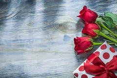 Scatola attuale con le rose rosse dell'arco sul concetto di feste del bordo di legno Immagini Stock Libere da Diritti