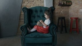 Scatola attuale d'apertura della ragazza adorabile di regali che si siedono sulla sedia in salone con l'albero di Natale video d archivio