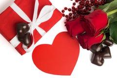 Scatola attuale di rosso con il nastro bianco, rose rosse, cuore di carta rosso Fotografia Stock