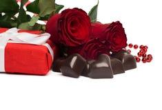 Scatola attuale di rosso con il nastro, le rose rosse e le caramelle bianchi Fotografia Stock
