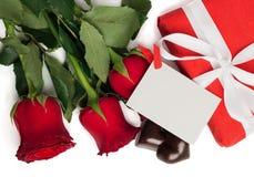 Scatola attuale di rosso con il nastro, le rose rosse, la cartolina e le caramelle Fotografie Stock Libere da Diritti