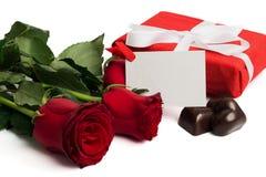Scatola attuale di rosso con il nastro, le rose rosse, la cartolina e le caramelle Immagine Stock