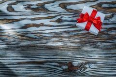 Scatola attuale di rosso con l'arco su fondo di legno immagine stock