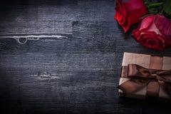 Scatola attuale fiorita delle rose rosse su fondo di legno Fotografia Stock Libera da Diritti