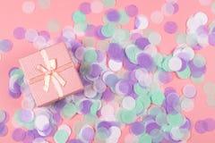 Scatola attuale su fondo rosa con i coriandoli multicolori fotografia stock