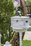 Scatola bianca d'annata vicino all'arco di cerimonia di nozze fotografia stock